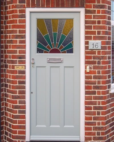 1920s front door with Art Deco sunrise leaded glass. Door spray painted light grey with chrome door furniture