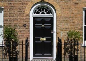 Georgian front door and fanlight door frame. Door painted black, frame painted white. Polished brass door funiture