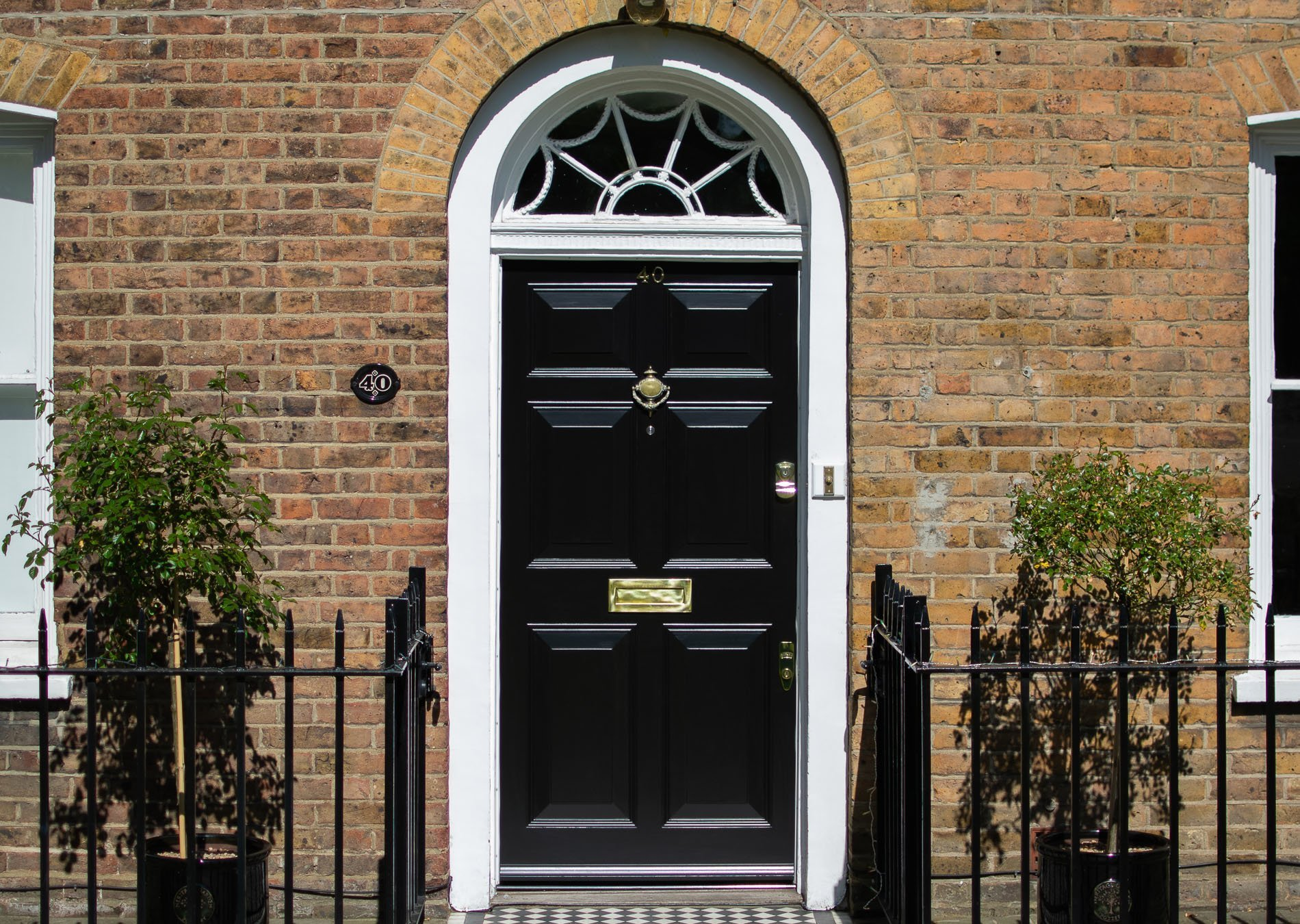 Georgian front door and fanlight door frame. Door painted black, frame painted white. Polished brass door funiture