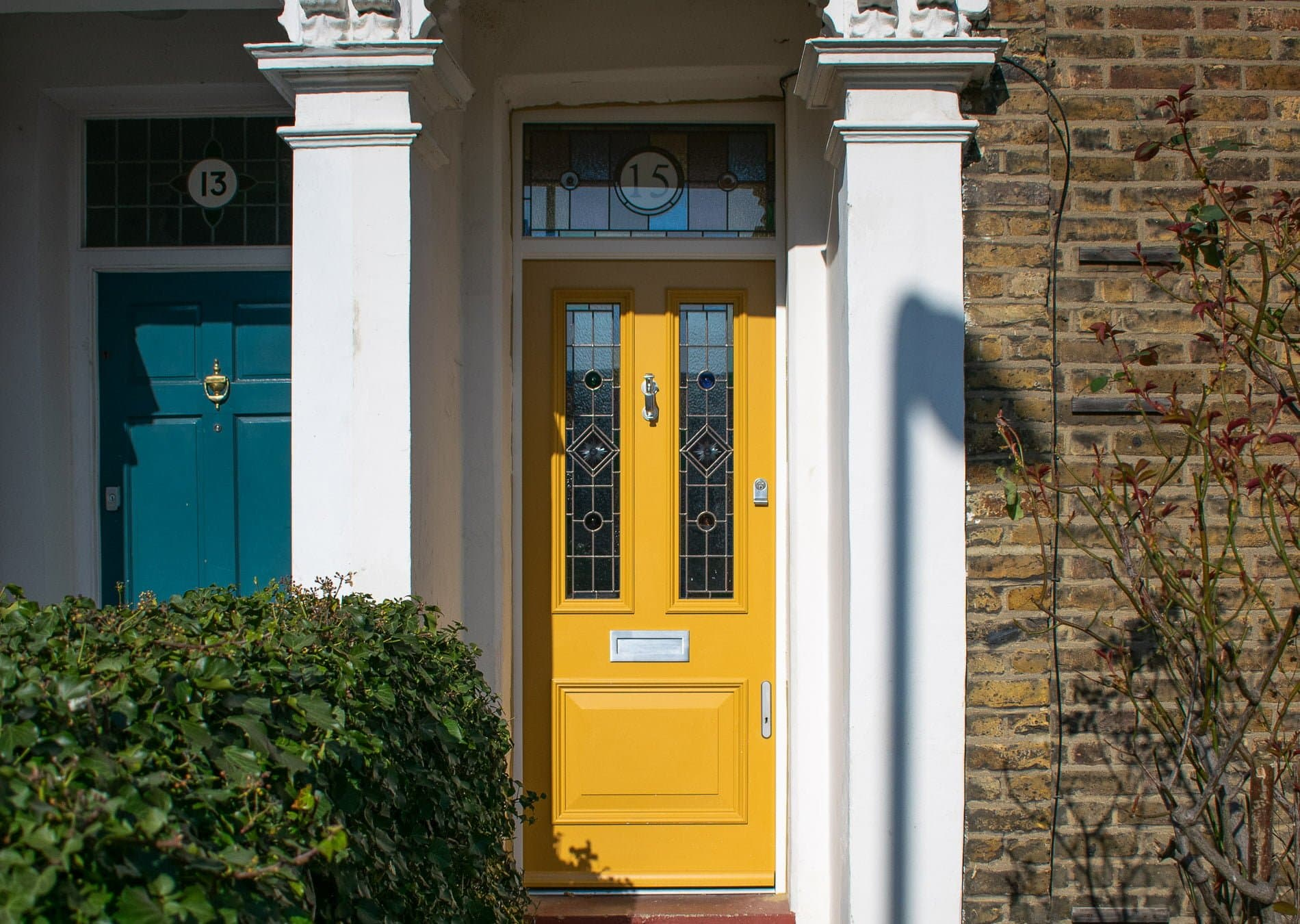 Victorian front door and fanlight frame. Door spray painted bright yellow. Stained glass in door and fanlight.