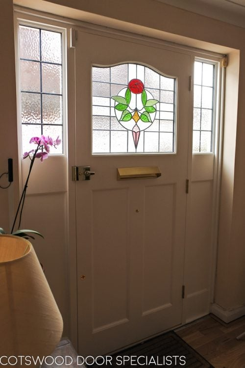 1920s Front entrance door with curved stained glass. Door fitted with brass locks and furniture. Hallway view of stained glass