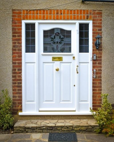 1920s Front entrance door with curved stained glass. Door fitted with brass locks and furniture. Fully spray painted satin white. Double sidelight door frame.