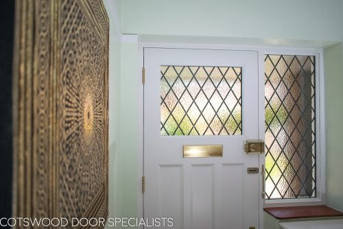 Inside of 1930s front door with leaded glass. Glazed door frame with diamond leaded glass. Brass door furniture. Inside of door painted white, viewed from hallway