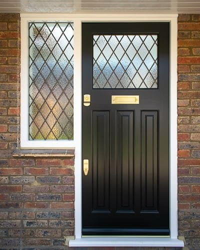 Black 1930s front door with leaded glass. Glazed door frame with diamond leaded glass. Brass door furniture