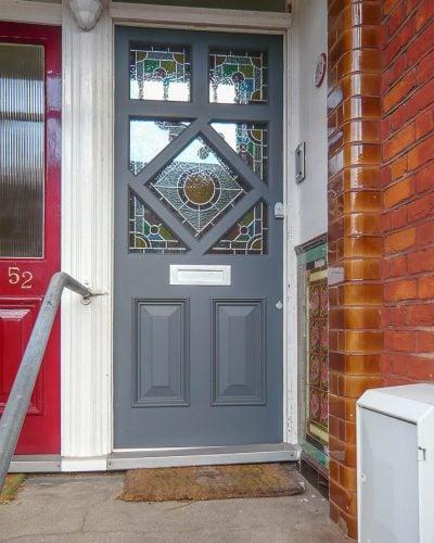 Diamond glazed Edwardian front door painted dark grey. Stained glass in door and satin chrome door furniture