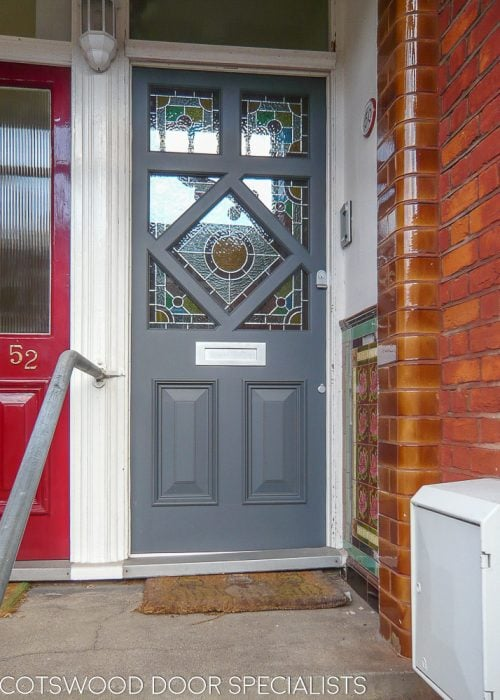 Diamond glazed Edwardian front door painted dark grey. Stained glass in door and satin chrome door furniture