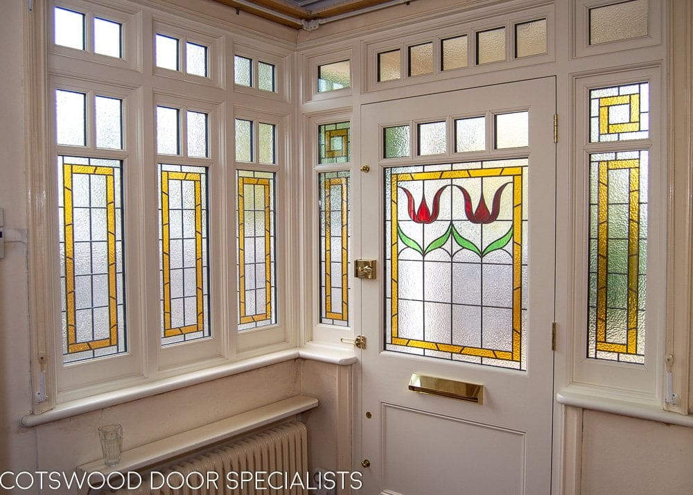 Edwardian front entrance with decorative frame. Stained glass to the door and frame. Door painted dark green. Edwardian hallway with stained glass in door