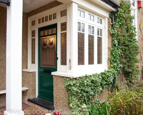 Edwardian front entrance with decorative frame. Stained glass to the door and frame. Door painted dark green. Edwardian porch with decorative side window