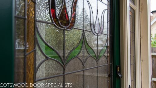 Edwardian front entrance with decorative frame. Stained glass to the door and frame. Door painted dark green. Edwardian porch. Flowers in stained glass
