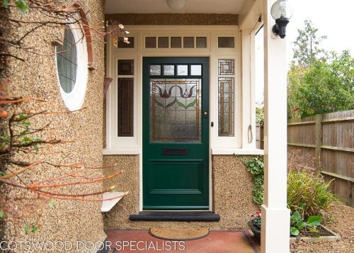 Edwardian front entrance with decorative frame. Stained glass to the door and frame. Door painted dark green. Edwardian porch
