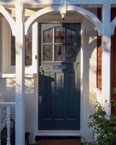 Edwardian six light front door. Door painted dark grey with white door frame. Stained glass to door and frame. Chrome door furniture with Banham locks