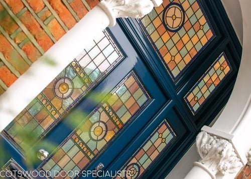 Extra wide Victorian front entrance door painted blue with stained glass. Door frame with glass to the sides and above the door