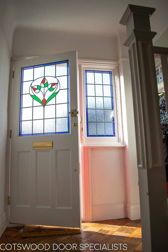 Late Edwardian red front door and sidelight frame. Shot from hallway of stained glass with light coming in