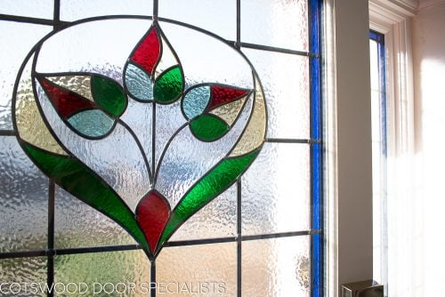 Late Edwardian red front door and sidelight frame. Shot from hallway of stained glass