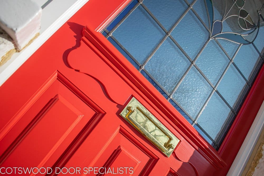 Late Edwardian red front door and sidelight frame. Door painted bright red. Stained glass in door and frame. Detail of shelf under glass