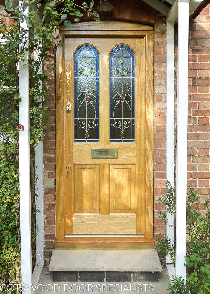 Natural wooden Victorian cottage front door with stained glass