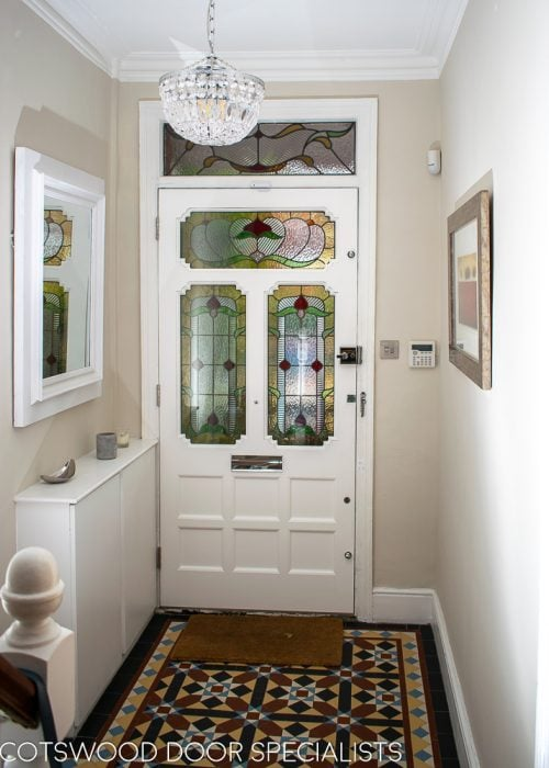 Ornate Edwardian front door stained glass. Door painted dark green inside painted white. View from hallway
