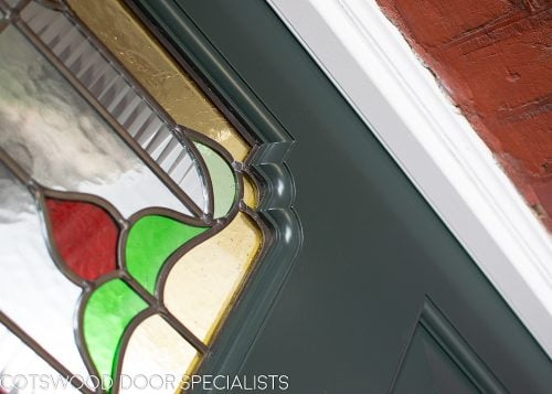 Ornate Edwardian front door stained glass. Door painted dark green. close up of mouldings