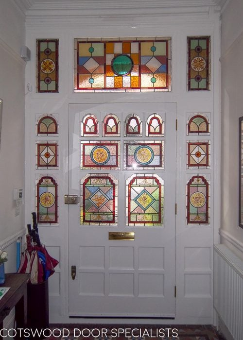 Ornate Victorian front door and frame with stained glass inside hallway