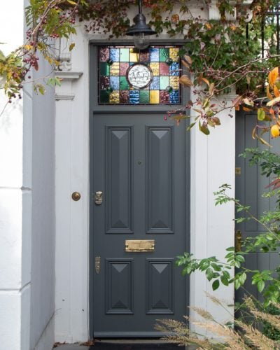 Dark grey Victorian front door solid with no glass. Stained glass to door frame