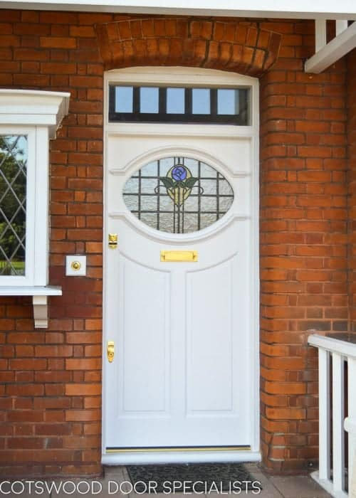 White 1920s front door with oval stained glass. Brass door furniture