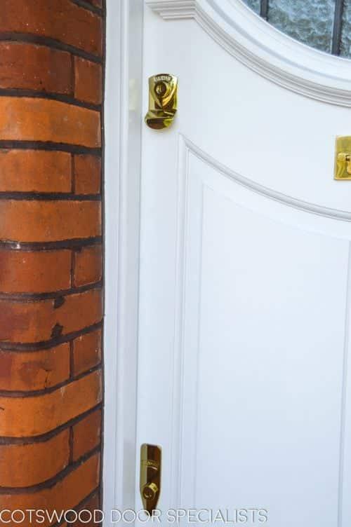 White 1920s front door with oval stained glass. Brass door furniture. Raised door panels. Brass door furniture and banham locks