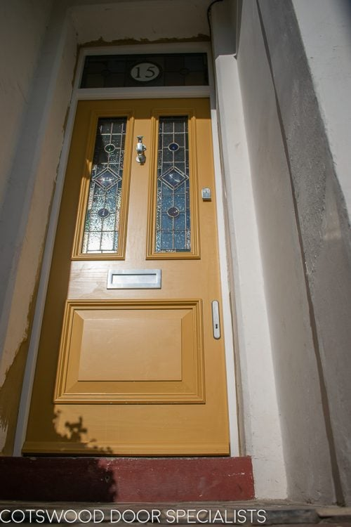 painted yellow Victorian front entrance door and frame with stained glass. Number in glass above door