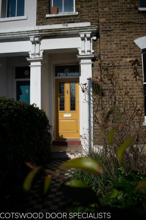 painted yellow Victorian front entrance door and frame with stained glass. Number in glass above door. traditional London home