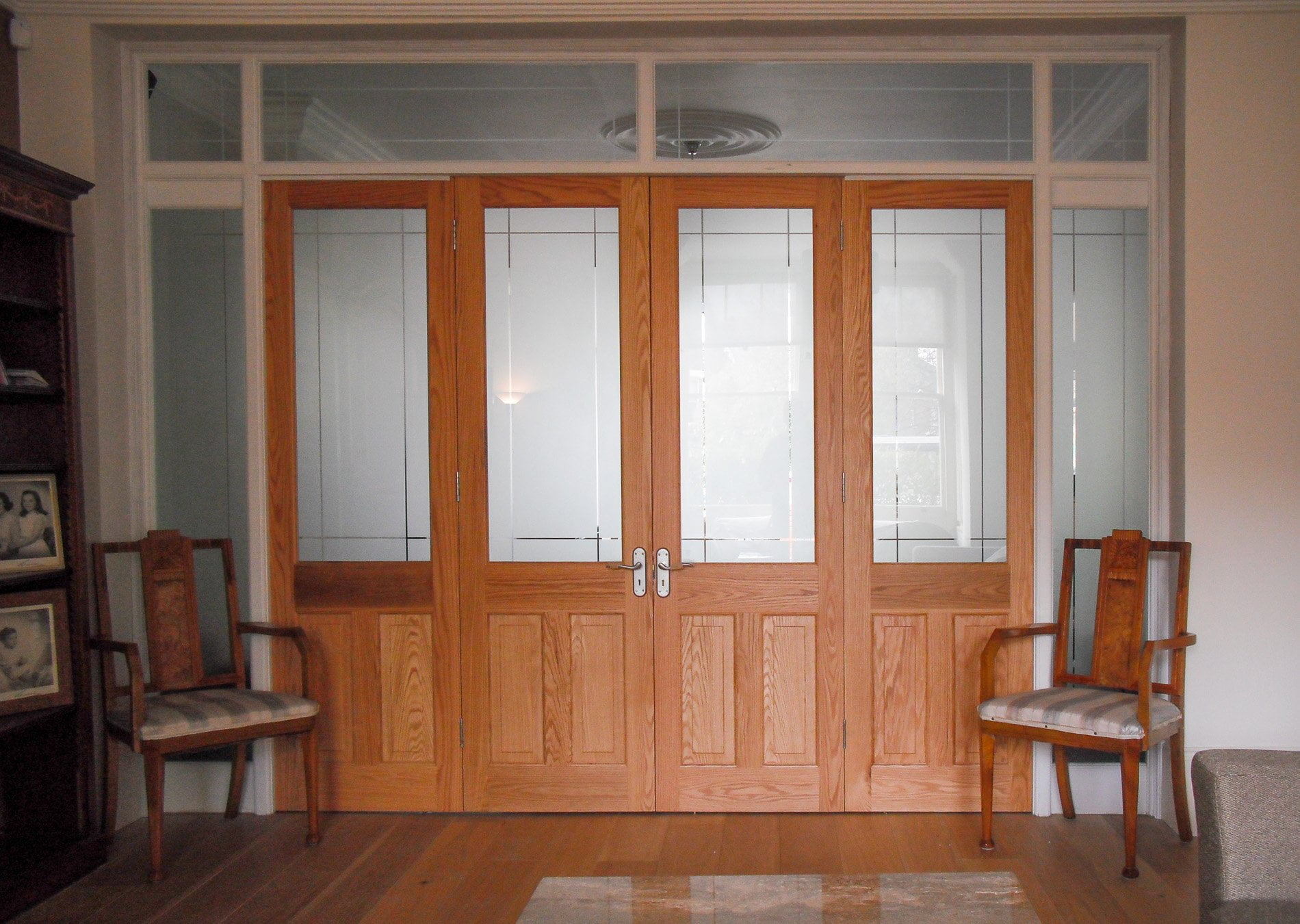 room dividing wooden doors. Stained natural finish doors and a white painted frame