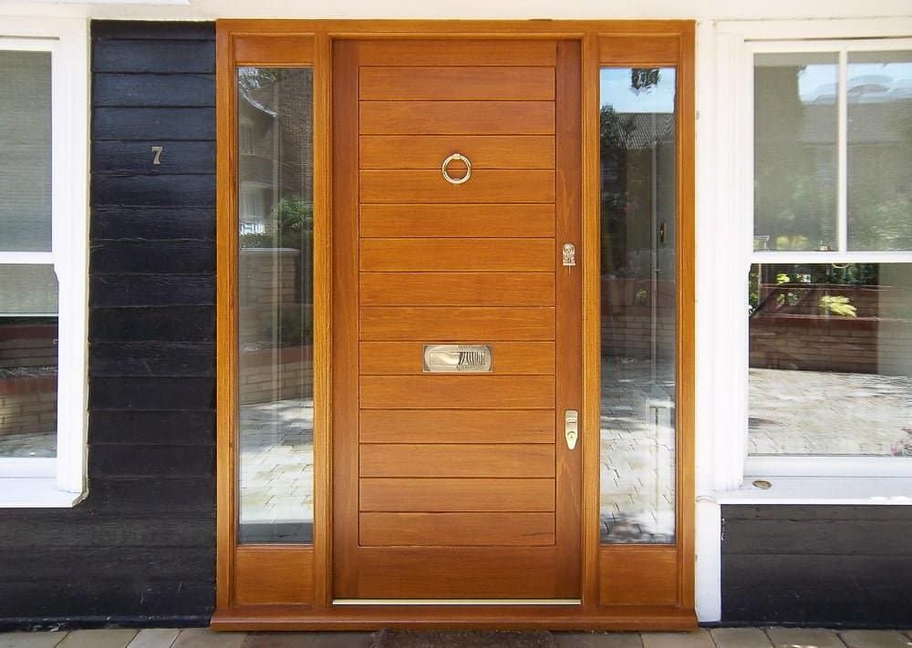 contemporary wooden front door and sidelight frame. Clear glass and polished chrome door furniture