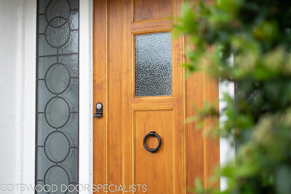 1930s style front door with small window. Natural finish wooden door. Black iron door furniture giving a rustic or Tudor appearance. Obscured glass to small window in door, frame with leaded Art Deco geometric design.