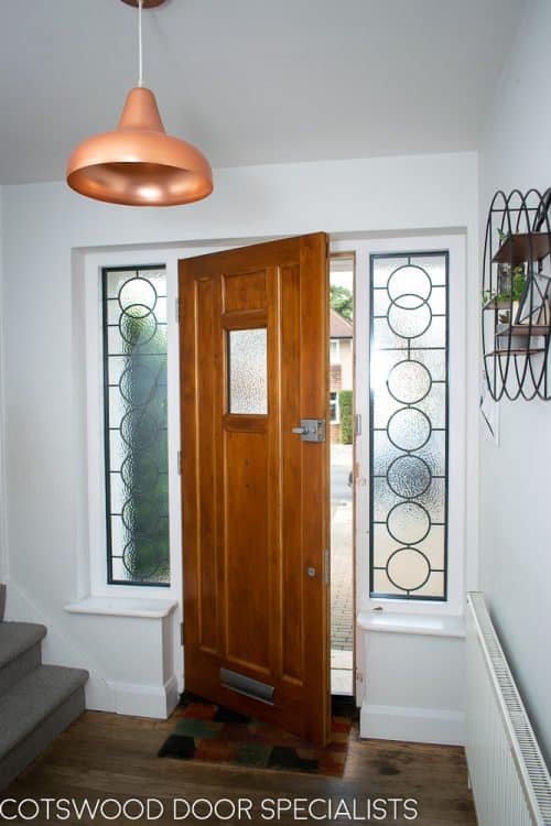 1930s style front door with small window. Natural finish wooden door. Black iron door furniture giving a rustic or Tudor appearance. Obscured glass to small window in door, frame with leaded Art Deco geometric design. Doorway viewed from hall
