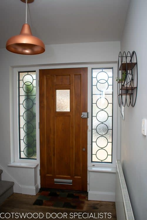 1930s style front door with small window. Natural finish wooden door. Black iron door furniture giving a rustic or Tudor appearance. Obscured glass to small window in door, frame with leaded Art Deco geometric design. Photo of hallway
