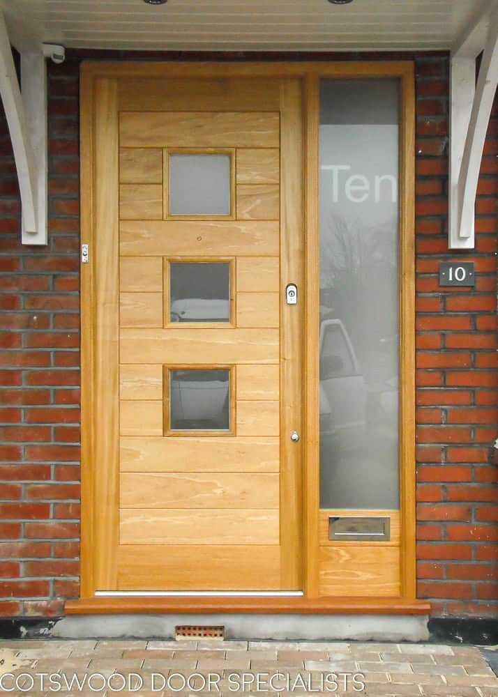 Contemporary glazed front door and sidelight frame. Etched glass in frame with number. Light stained natural wood