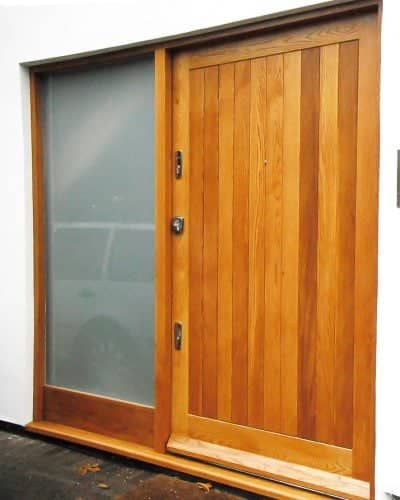 Extra wide contemporary front door. Light stained natural wood. Polished chrome door furniture. Sidelight frame fitted with satin etched glass