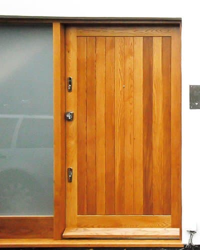 Extra wide contemporary front door. Light stained natural wood. Polished chrome door furniture