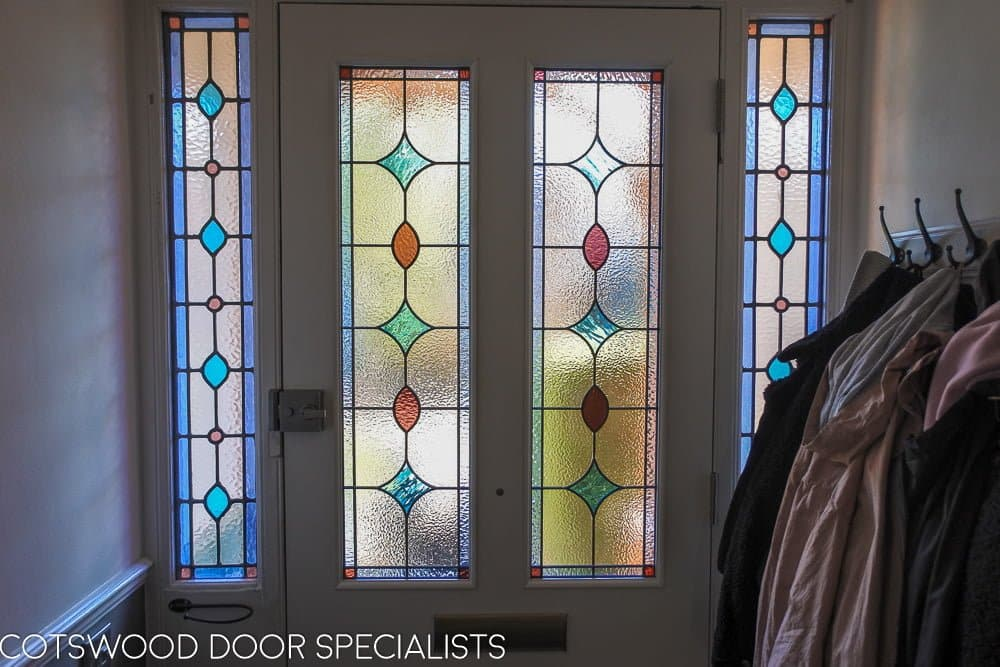Late Victorian front door painted white internally. Light shining though the leaded glass