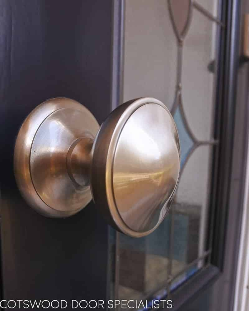 Late Victorian style dark blue painted front door. Door and frame with stained glass. Satin chrome door furniture. Closeup of door knob
