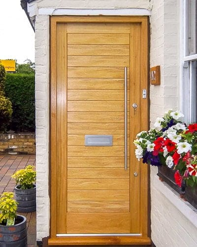 Light wooden contemporary front door and frame. Solid door with no glass. Satin chrome door furniture with long bar handle