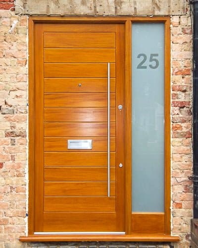 Modern wooden door and sidelight frame. Solid door with horizontal boards. Etched glass in sidelight with clear number. Satin chrome door furniture with long bar handle.