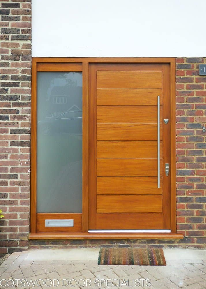 Wide boarded contemporary front door. Sidelight frame with etched glass. Simple door furniture with long bar handle. Satin chrome banham locks