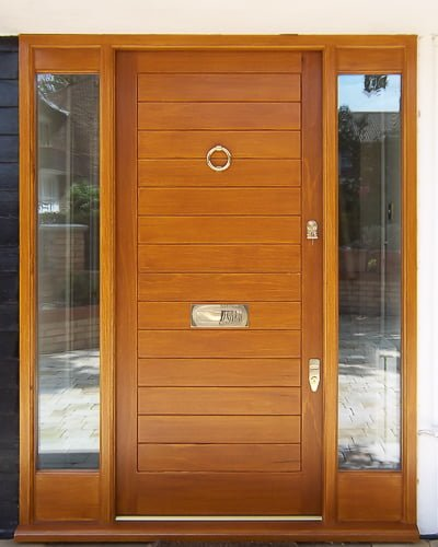 Wide wooden contemporary front door. Double sidelight frame with clear double glazed units. Polished chrome door furniture. Medium stained natural wood