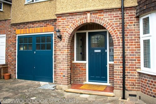 1930s stained glass front door painted farrow and ball hague blue. Double 1930s sidelight frame with brick below the sidelights. Stained glass to door and door frame. Satin chrome door furniture. Picture with matching garage doors