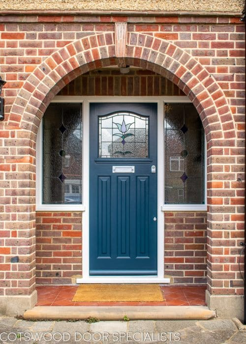 1930s stained glass front door painted farrow and ball hague blue. Double 1930s sidelight frame with brick below the sidelights. Stained glass to door and door frame. Satin chrome door furniture