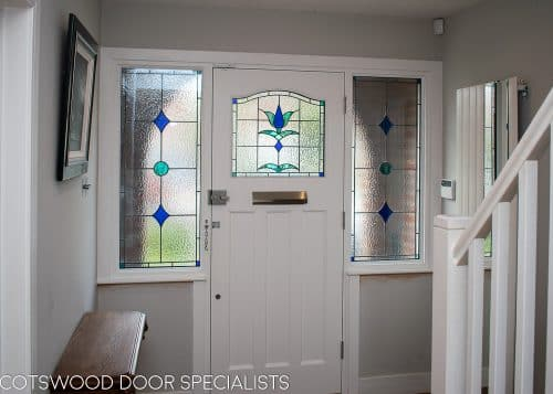 1930s stained glass front door painted farrow and ball hague blue. Double 1930s sidelight frame with brick below the sidelights. Stained glass to door and door frame. Satin chrome door furniture. View of door from inside hallway