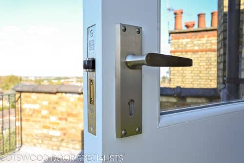 Balcony french door made in Accoya wood and painted white. Clear double glazed glass and satin chrome door fittings. Fitted into a London balcony. Closeup of door handle
