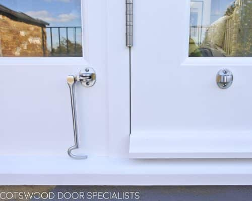 Balcony french door made in Accoya wood and painted white. Clear double glazed glass and satin chrome door fittings. Fitted into a London balcony. Closeup of cabin hook to retain door
