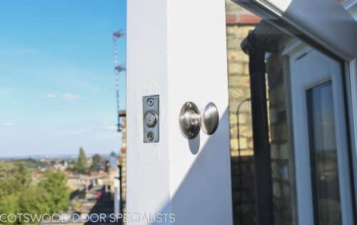 Balcony french door made in Accoya wood and painted white. Clear double glazed glass and satin chrome door fittings. Fitted into a London balcony. Closeup of door bolt