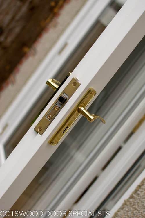 Brass door handle on wooden french doors. Lock closeup