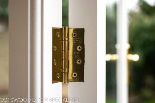 Brass door hinge on wooden french doors